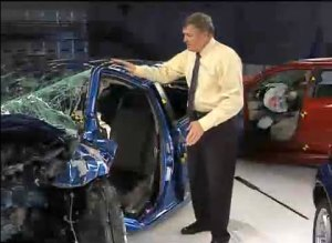 "(caption: Standing by a compact car, crushed in a test against a mere mid-sized car: ""The laws of physics can't be repealed. Even with modern safety features like multiple air bags, people in small, light cars are always at a disadvantage in crashes."" -- Russ Rader, Insurance Institute for Highway Safety)"